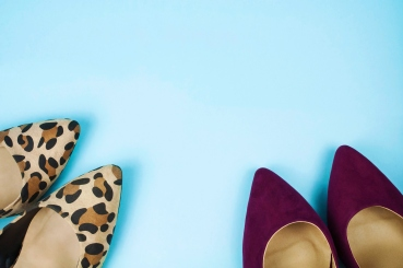 Two pairs of stiletto shoes on light blue background.