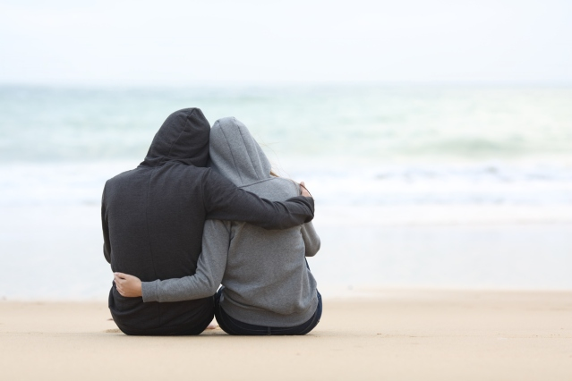 Couple of teenagers hugging watching sea